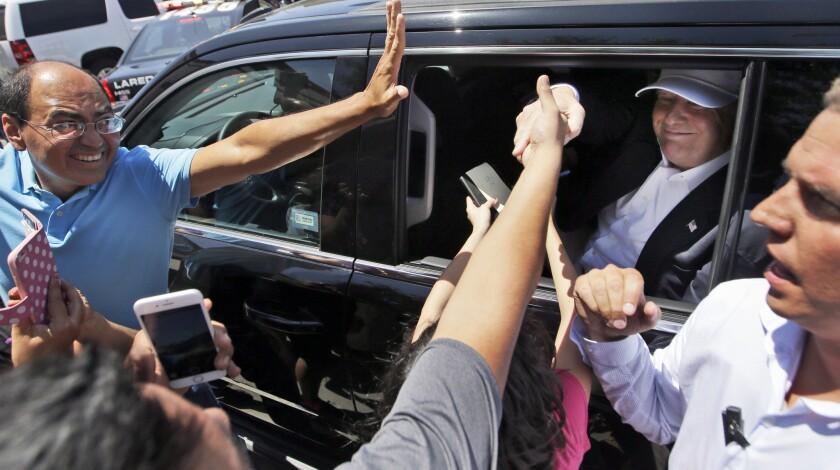"""Simpatizantes se acercan a saludar al precandidato presidencial republicano Donald Trump tras una breve parada para hablar con simpatizantes y medios de comunicación en Laredo, Texas, el jueves 23 de julio de 2015. Trump visitó la frontera con México el jueves y vaticinó que los hispanos lo amarán _ """"ya lo hacen""""_ pues como presidente regresará los empleos que se han ido al extranjero y le dará más oportunidades a aquellos que viven legalmente en Estados Unidos."""