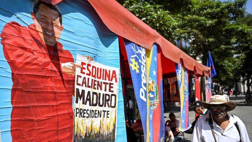 A man walks past a painting depicting late Venezuelan President Hugo Chavez in Caracas on Friday.