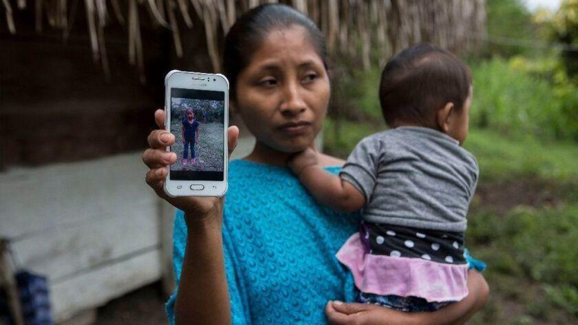 Claudia Maquin, 27, shows a photo of her daughter, Jakelin Amei Rosmery Caal Maquin, in Raxruha, Guatemala, on Dec. 15.