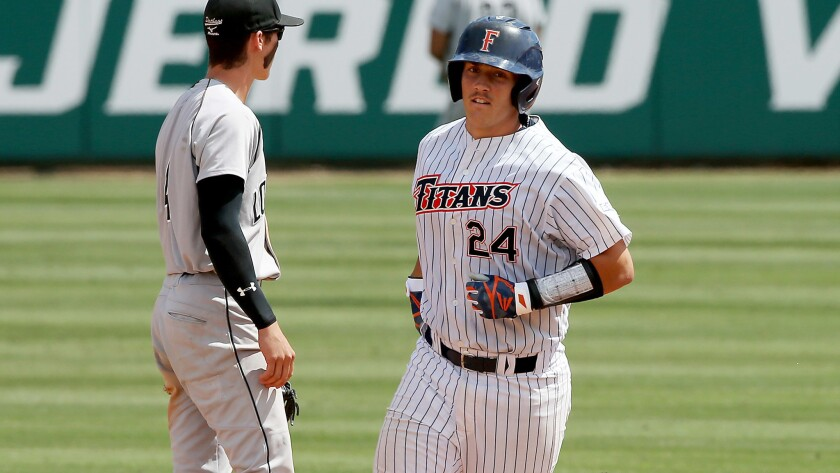 Fullerton catcher Chris Hudgins rounds the bases after hitting a two-run home run against Long Beach