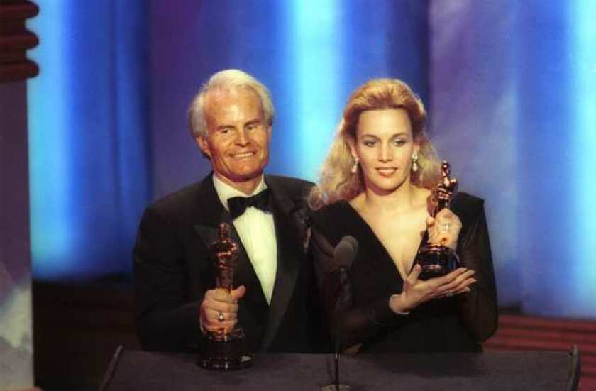 """Richard D. Zanuck, left, with Lili Fini Zanuck, accepting best picture Oscars for """"Driving Miss Daisy"""" in 1990 at the Academy Awards in Los Angeles."""