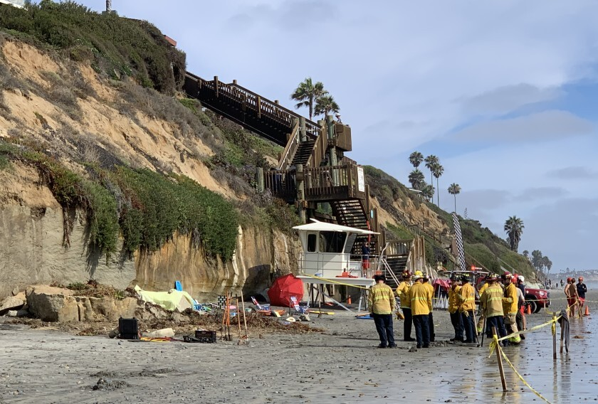 Rescue workers gather at the base of an Encinitas, Calif., beach bluff that collapsed.
