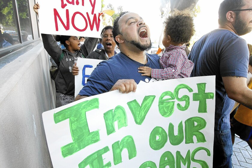Gilbert Johnson of South Los Angeles holds his 1-year-old son Josiah during a rally at L.A. Unified headquarters.