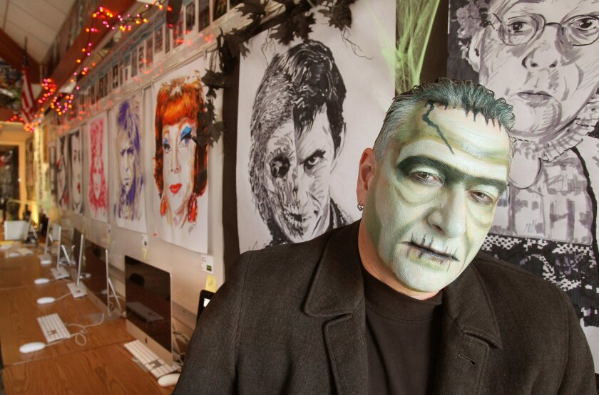 Portrait of teacher Paul Messerle in a Halloween costume in his graphic arts classroom at Rancho Bernardo High School that's decorated with the 30 monster portraits he created.