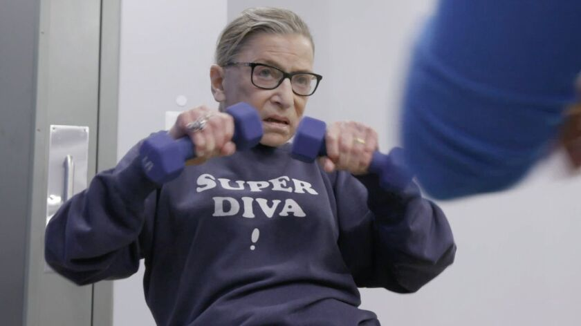 "Justice Ruth Bader Ginsburg lifts weights wearing a ""Super Diva"" sweatshirt."