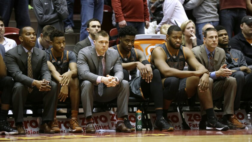 Texas players and coaches sit on the bench during the second half of the team's NCAA college basketball game against Iowa State, Saturday, Feb. 13, 2016, in Ames, Iowa. Iowa State won 85-75. (AP Photo/Charlie Neibergall)