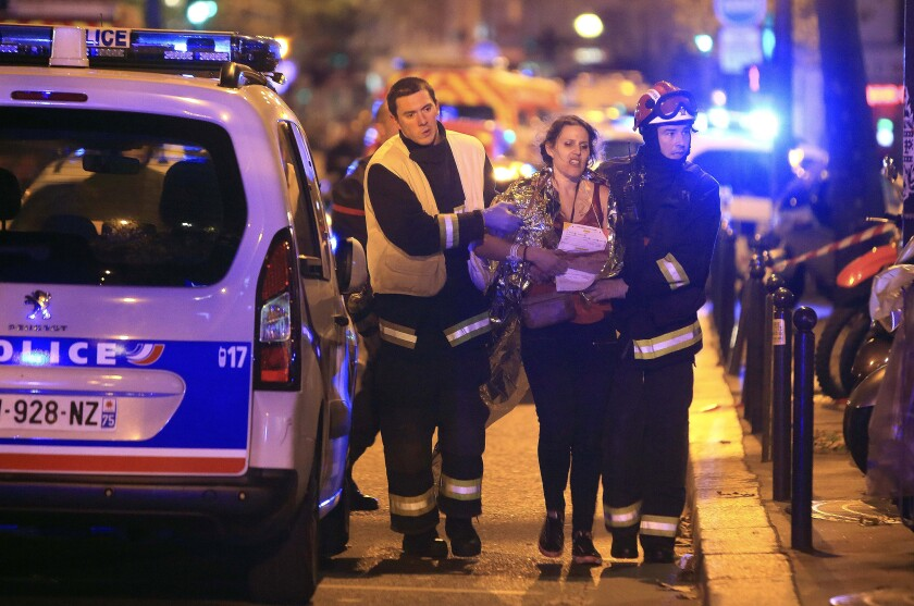 Rescue workers helping woman after a terrorist attack in Paris