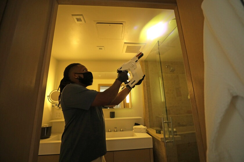 A Malibu Beach Inn employee shows how a room is disinfected.