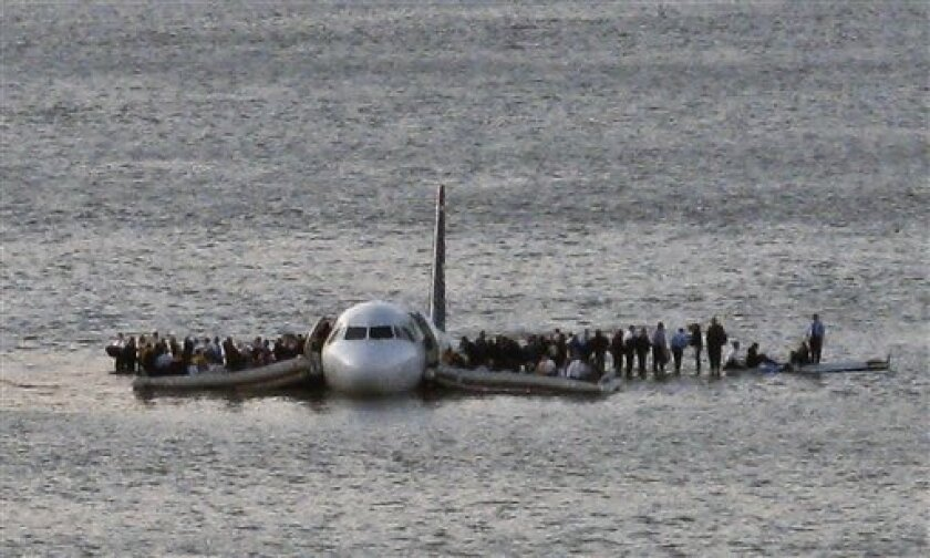"""In this Thursday Jan. 15, 2009 file photo, airline passengers wait to be rescued on the wings of a US Airways Airbus 320 jetliner that safely ditched in the frigid waters of the Hudson River in New York, after a flock of birds knocked out both its engines. A reader-submitted question about the miracle crash landing in the Hudson River is being answered as part of an Associated Press Q&A column called """"Ask AP"""" (AP Photo/Steven Day)"""