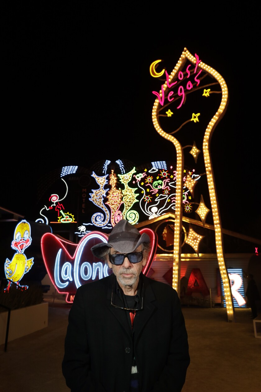 "Tim Burton pauses in front of ""Neon Grid Wall"" and ""Lost Vegas Sign Tower"" at his ""Lost Vegas"" exhibit at the Neon Museum in Las Vegas."