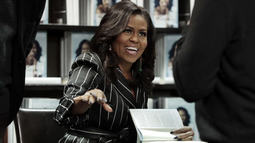 "Former First Lady Michelle Obama signs copies during an appearance for her book, ""Becoming,"" in New York. Sales for Obama's memoir have topped 3 million, and the former first lady is extending her book tour into 2019."