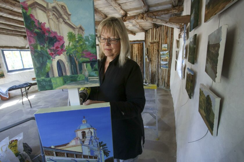City of Carlsbad Curator of Exhibits, Karen McGuire, hangs paintings of mostly county scenes, Balboa Park, top, by Diane O'Connell, Mission San Luis Rey, bottom, by Kyung Drury, Thursday at Deedie's House, part of the Leo Carrillo Ranch Historic Park in Carlsbad.