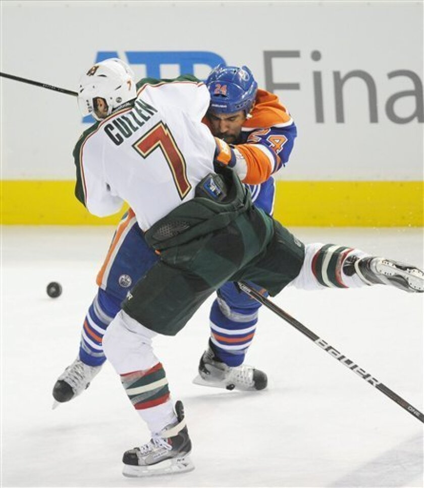 Edmonton Oilers' Theo Peckham, 24, and Minnesota Wild Matt Cullen collide during the overtime period of NHL hockey action in Edmonton on Wednesday, Nov. 30, 2011. (AP Photo/The Canadian Press, John Ulan)
