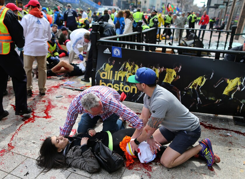 Sydney Corcoran is tended to at the finish line of the Boston Marathon on Monday. This photo ran in many newspapers across the nation Tuesday, but her identity was not immediately known.