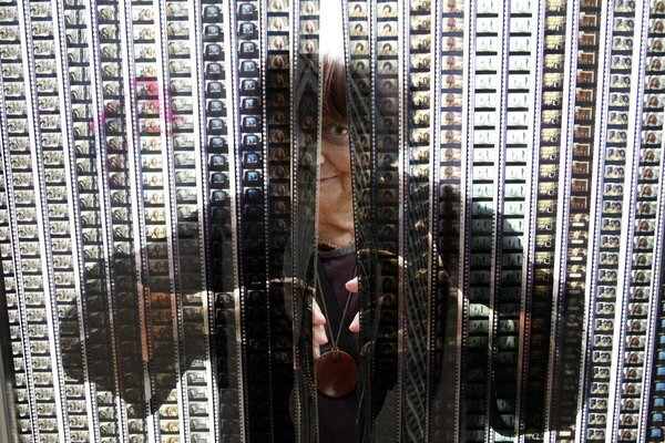 """Agnes Varda peers through the celluloid curtain of her art installation """"My Shack of Cinema"""" at LACMA, her ode to filmmaking. The museum takes a look at the French auteur's time in the Golden State in the exhibition """"Agnes Varda in Californialand."""""""