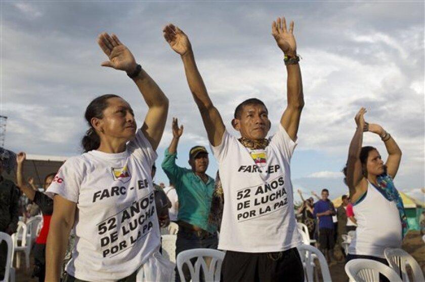 """Rebeldes de las Fuerzas Armadas Revolucionarias de Colombia hacen la ola en Sabanas del Yarí, Colombia, mientras ven imágenes en directo en las pantallas de la firma del acuerdo de paz entre el gobierno y las FARC en Cartagena para poner fin a más de cinco décadas de hostilidades, el lunes 26 de septiembre del 2016. En sus camisetas se lee: """"52 años de lucha por la paz""""."""