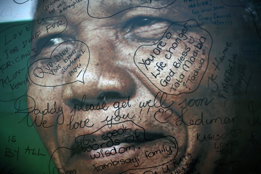 Messages left by supporters are seen on a poster of former South African President Nelson Mandela outside his Soweto home.