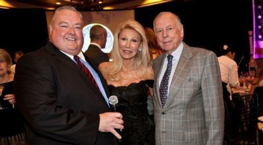 Auctioneer Steve Lewandowski stands with Rancho Santa Fe philanthropists T. Boone and Madeleine Pickens last month at the Del Mar Country Club for the annual SEAL-Naval Special Warfare Foundation benefit. Photo courtesy of elegantphotography.co