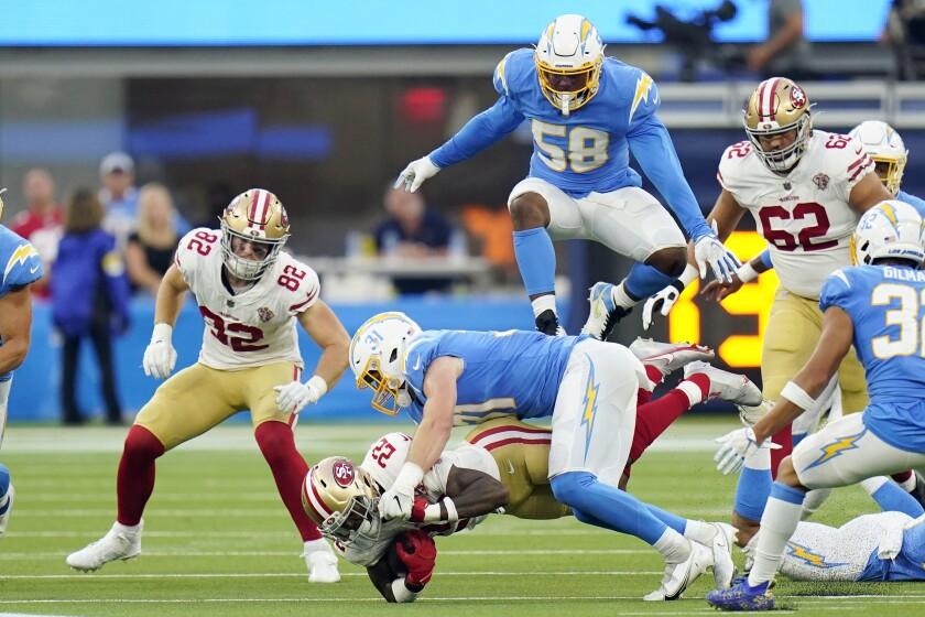 San Francisco 49ers running back Wayne Gallman, bottom, is tackled by Chargers linebacker Nick Niemann.