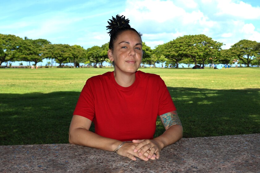 """Ashley Maha'a sits in a park in Honolulu on June 22, 2021. """"I've met so many people on the mainland, and so, so, so many of them have told me that when they were being trafficked nationally, they would be flown here for a period of time and work here when things were slow, because the demand is so high,"""" Maha'a says. (AP Photo/Audrey McAvoy)"""