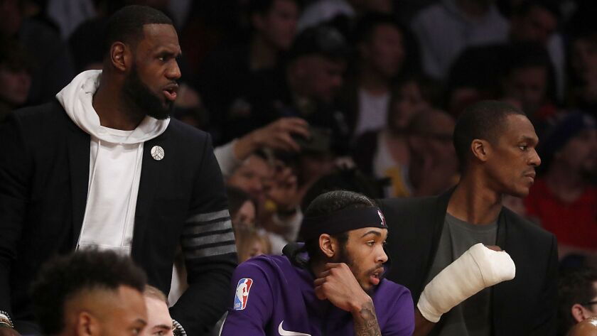 Lakers' LeBron James, left, Brandon Ingram (center) and Rajon Rondo (right) watch the game against the Clippers from the bench in the second quarter Friday night at Staples Center.