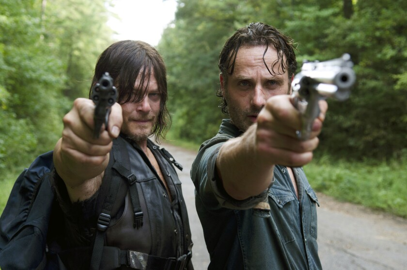 "Daryl Dixon (Norman Reedus) and Rick Grimes (Andrew Lincoln) draw their guns when threatened by a stranger with impressive fighting skills on ""The Walking Dead."""