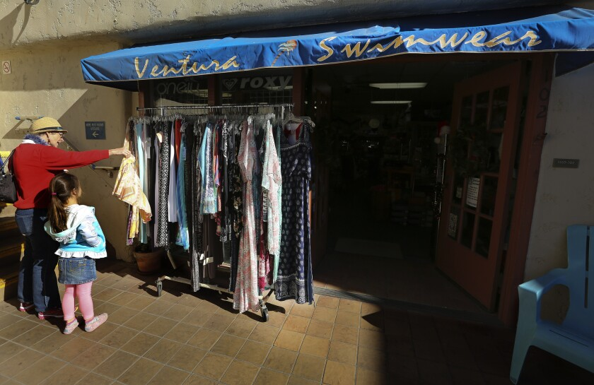 Shoppers check out the rack in front of the entrance to Ventura Swimwear at Ventura Harbor Village.
