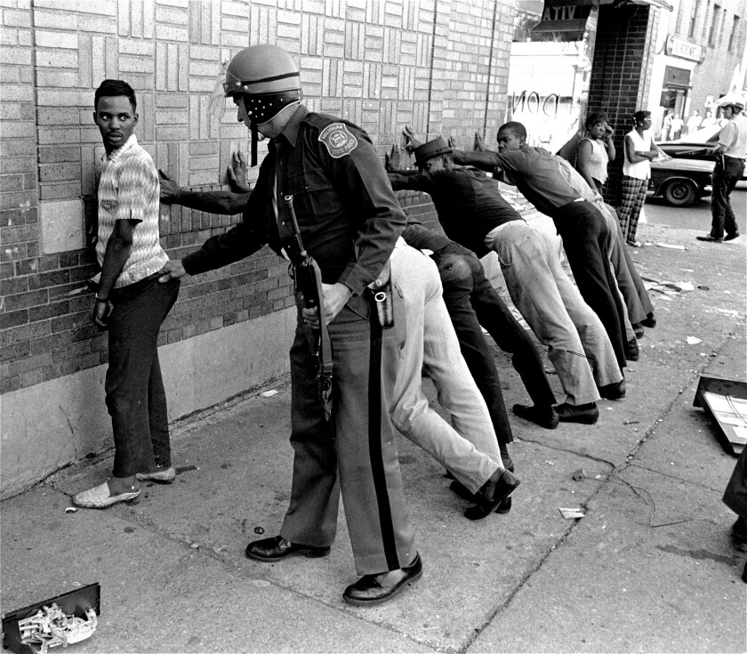 A police officer searches a youth as others are lined up against a wall.
