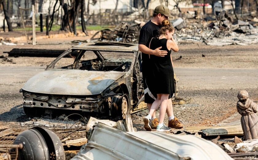 Two people hug while surrounded by ruins of a home destroyed by fire