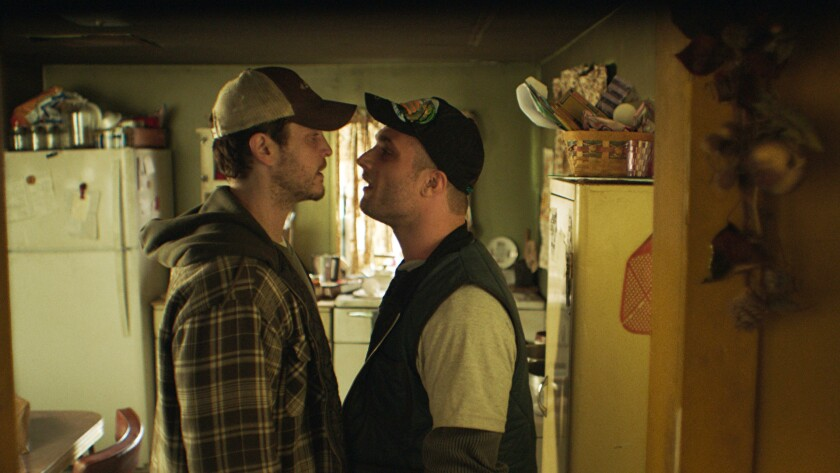 """Two men in trucker caps go face to face in a kitchen in the movie """"The Evening Hour."""""""