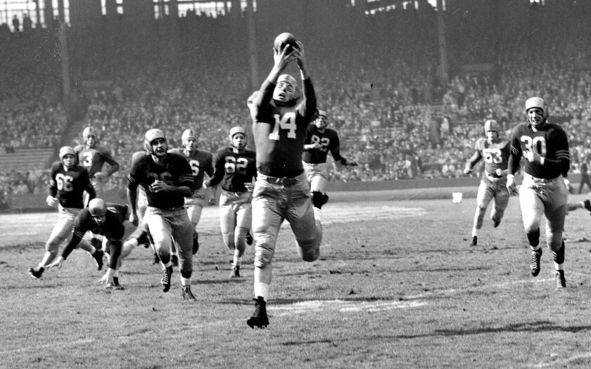 FILE - In this Nov. 1, 1952, file photo, Notre Dame's John Lattner (14) reaches for a pass during a college football game against Navy in Cleveland, Ohio. Lattner, the 1953 Heisman Trophy winner who helped lead Notre Dame to a 9-0-1 record and a No. 2 ranking in Frank Leahy's final year as coach, h