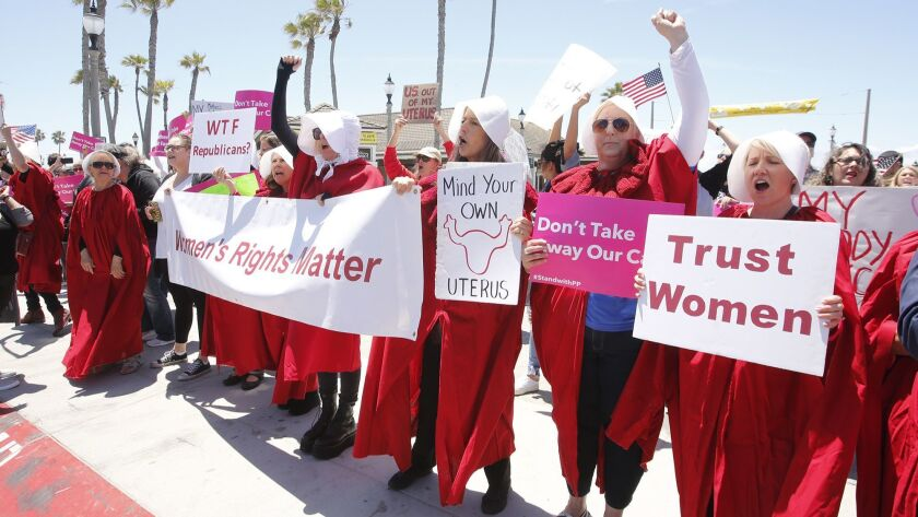 Dressed as Handmaidens, participants with Tuesdays Without Dana protest the attempt to reverse Roe v