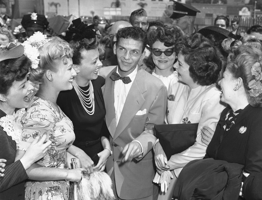 This photo was described as fans surrounding crooner Frank Sinatra as he arrives in Pasadena, Calif., Aug. 11, 1943, for Hollywood film and singing engagements. In truth, though, the photo may have been staged in New York in advance for publicity purposes.  (AP Photo/John T. Burns)