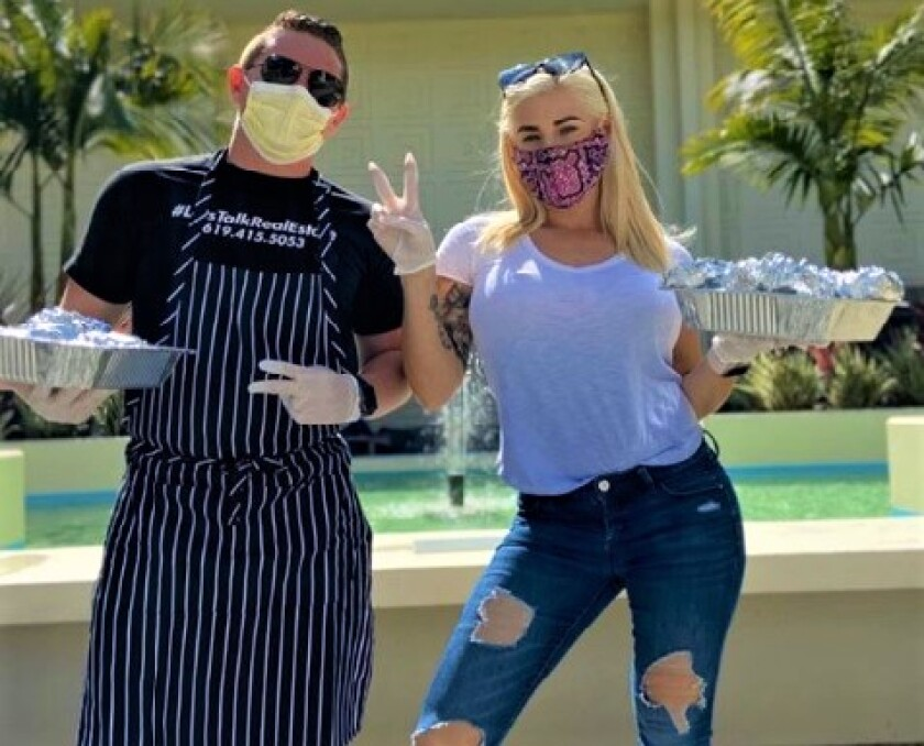 San Diego chef Lauren Lawless, right, sports her face mask as she holds a tray of food she prepared for workers on the pandemic frontlines.