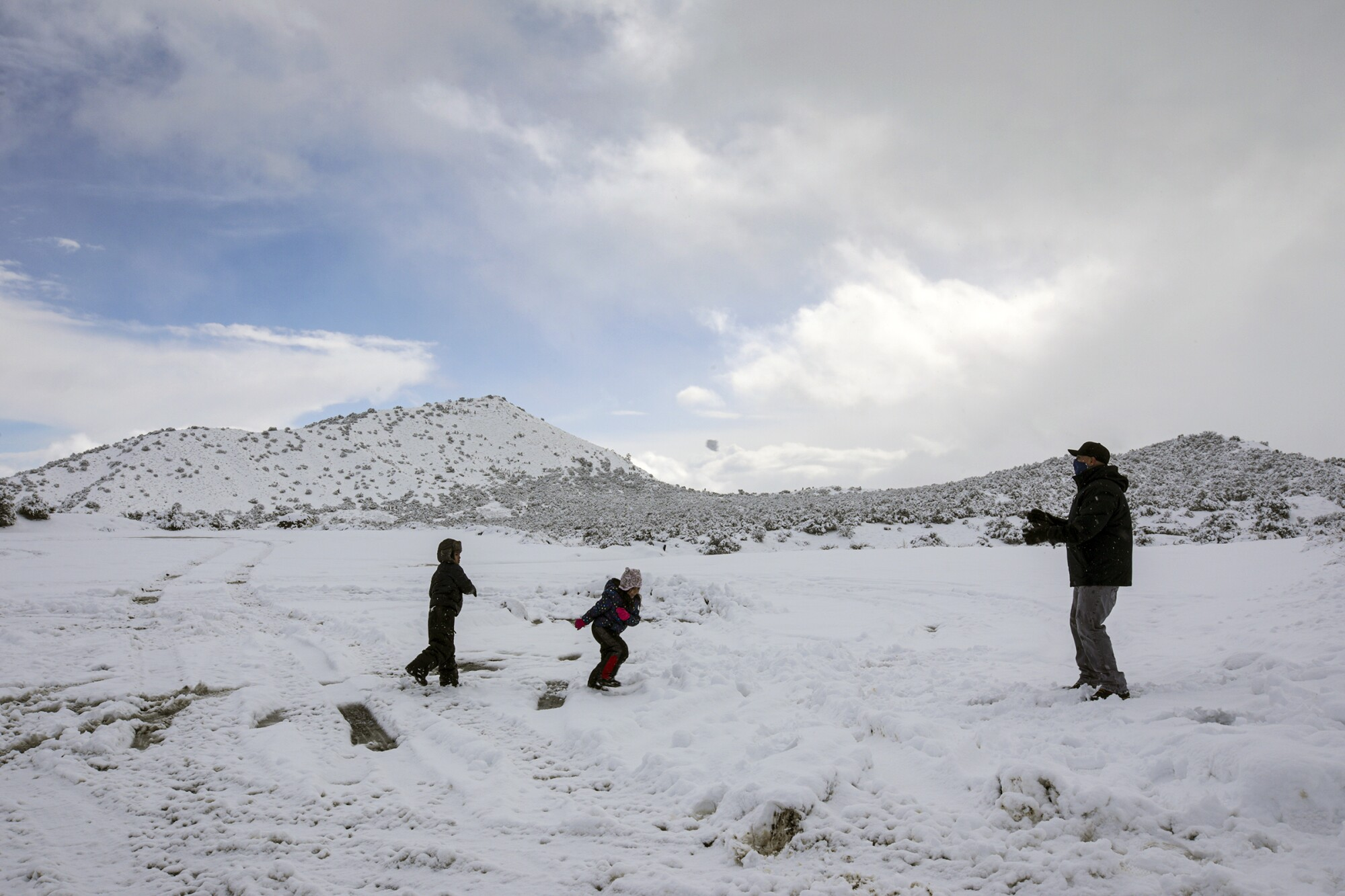 Adrian Rios and his children, Ian, left, and Susan play along Highway 138  in Phelan.