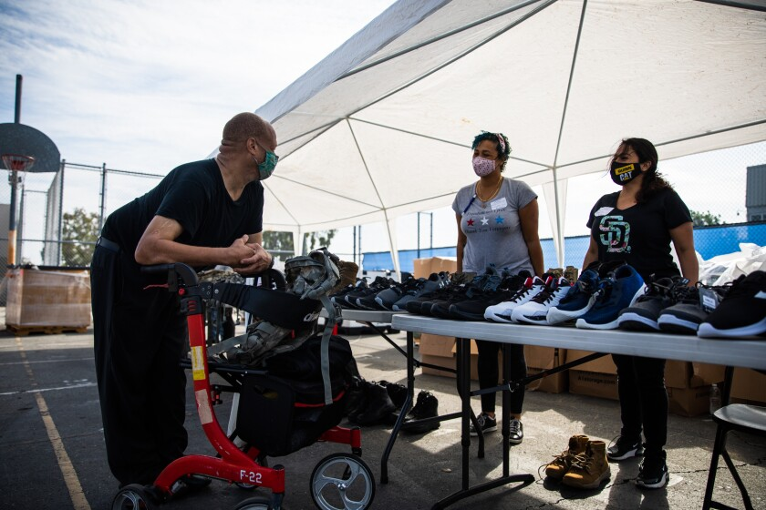 """U.S. Army veteran Allen Gallagher speaks with volunteers during the annual """"Stand Down."""""""