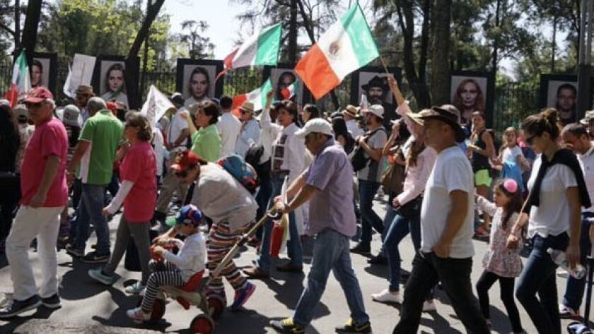 Marchers in Mexico City along Paseo de la Reforma protest the immigration and trade policies of President Trump. Mexican police said more than 20,000 people participated in the peaceful march Sunday.