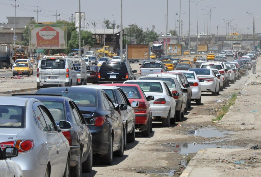 Iraqi motorists wait in line to get fuel for their vehicles Wednesday in Kirkuk following an assault on Iraq's main Baiji oil refinery.