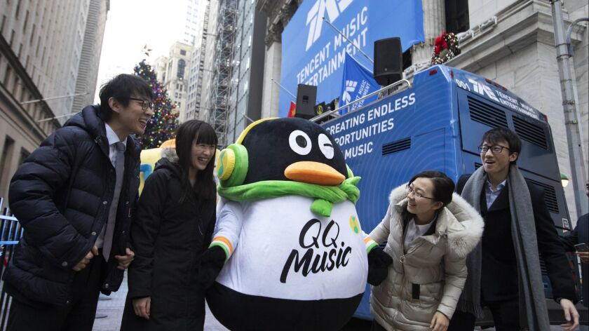 Tencent Music Entertainment employees pose with the QQ Music mascot for a photo in front of the New