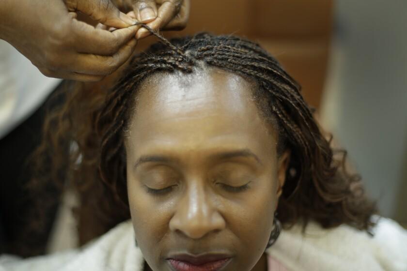 Shelly Smith braids hair for Bridget Dunmore at her salon, Braid Heaven Tuesday, Jan. 28, 2020, in Kansas City, Kan.