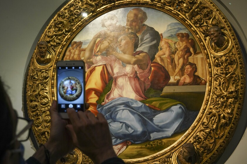 "A member of the media takes a picture of 15th century painting ""Doni Tondo"" by Michelangelo Buonarroti, during a press tour of the Uffizi museum on the day off its reopening, in Florence, Wednesday, June 3, 2020. The Uffizi museum reopened to the public after over two months of closure due to coronavirus restrictions. (AP Photo/Andrew Medichini)"