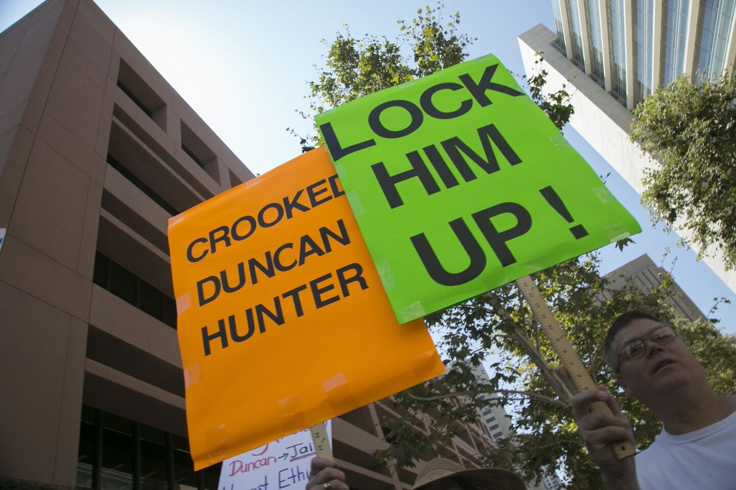 A protester who didn't want to give his name held a sign outside of the Federal Courthouse where 50th congressional district representative Duncan D. Hunter was arraigned in in San Diego on charges that he and his wife Margaret Hunter misused $250,000 in campaign contributions.