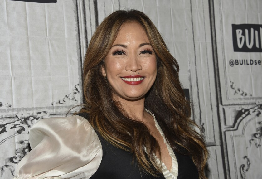 Carrie Ann Inaba smiles in a cream silk blouse and black vest.