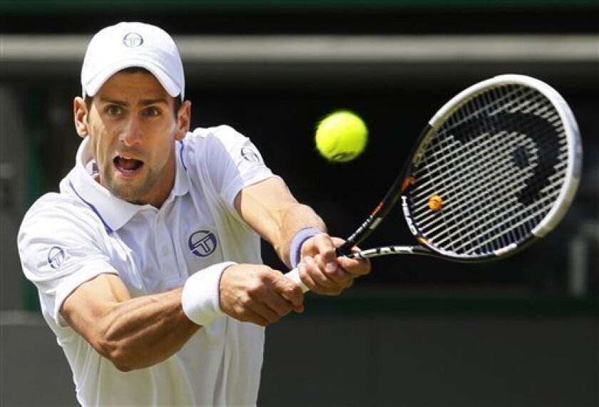Serbia's Novak Djokovic returns a shot to South Africa's Kevin Anderson during their match at the All England Lawn Tennis Championships at Wimbledon, Thursday, June 23, 2011. (AP Photo/Kirsty Wigglesworth)