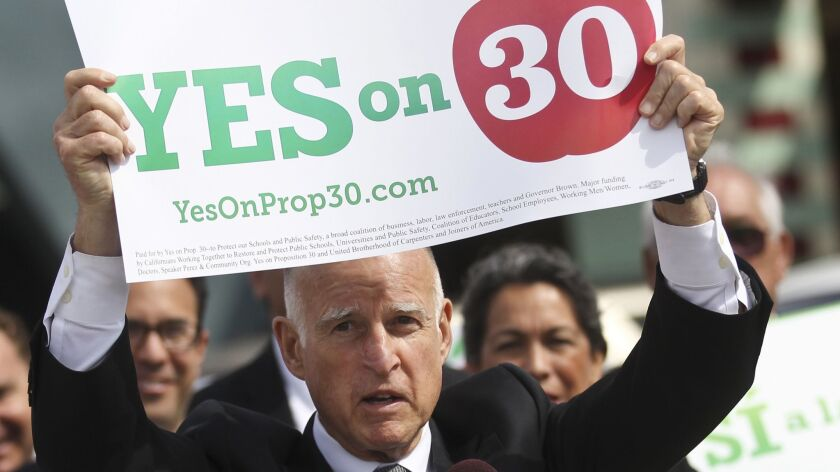 Gov. Jerry Brown holds up a sign in support of Proposition 30 while visiting a San Diego school on Oct. 23, 2012, in San Diego. The ballot measure passed with 55% of the vote.