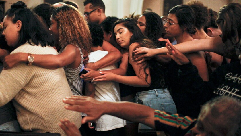 The McCarty Memorial Christian Church congregation comes together to embrace a man who recently lost his brother at the hands of police.