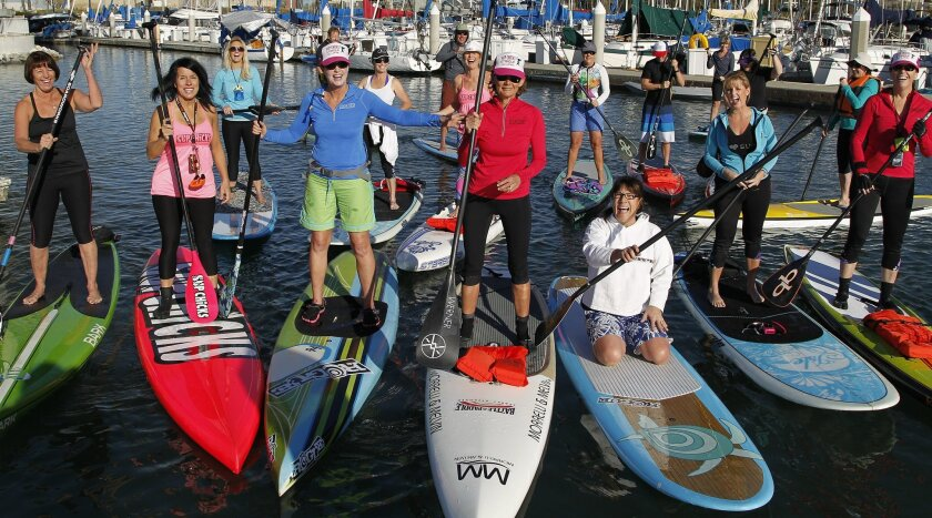 Members of the SUP Chicks gather in Oceanside Harbor to stand up paddle (SUP) on Tuesday in Oceanside, California.