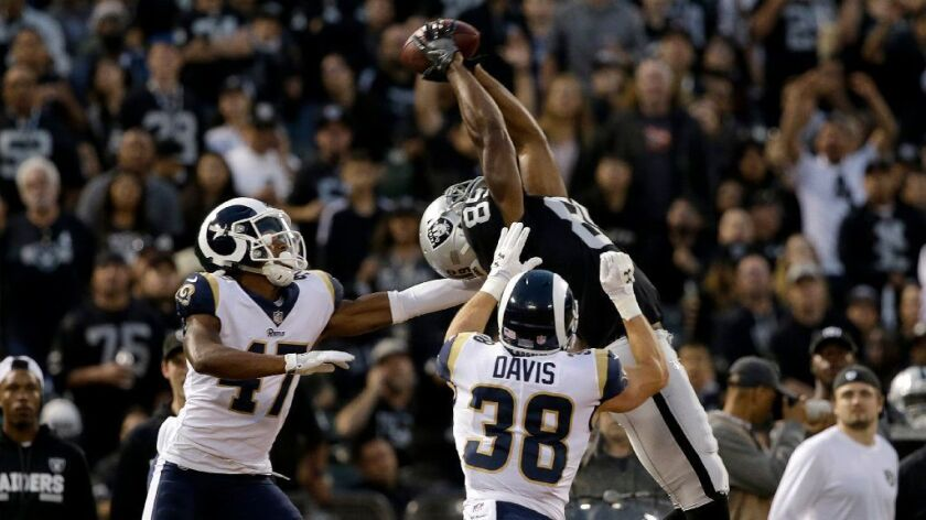 Raiders receiver Amari Cooper goes up and gets a football above Rams cornerback Kevin Peterson (47)