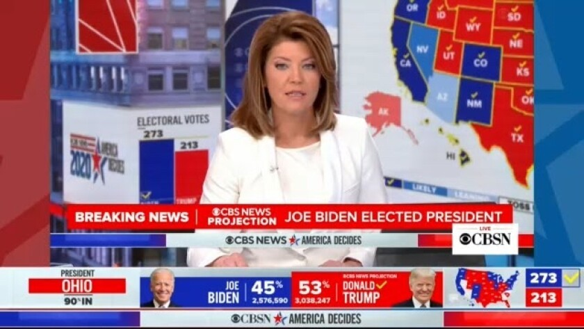 CBS News anchor Norah O'Donnell sits at anchor desk, surrounded by red, white and blue graphics.