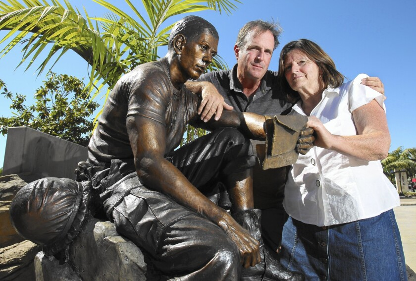 Rico and Mary Ann Pinamonti with the statue of their brother, Marine Pvt. Ernie Pinamonti, at Veterans Memorial Park in Vista.